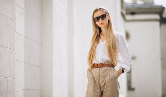 Roupas e acessórios atemporais: quais são e porquê apostar - Mulher vestindo uma camisa branca e uma calça bege